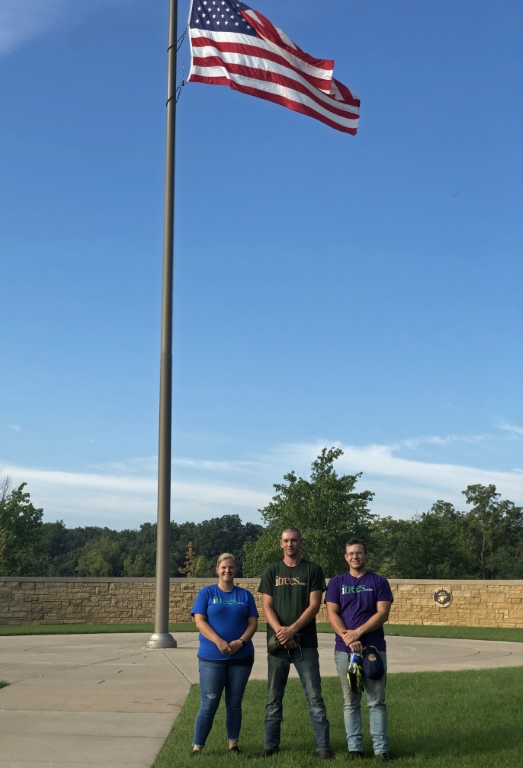 Marlee, Kyle and Ray in front of the American Flag